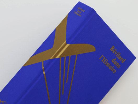 Tranche de couverture du livre Bévilard dans l'Histoire sur laquelle figure une sérigraphie dorée. Le livre est recouvert d'une toile bleu roi. Les couleurs bleu roi et or correspondent aux couleurs de la commune de Bévilard.