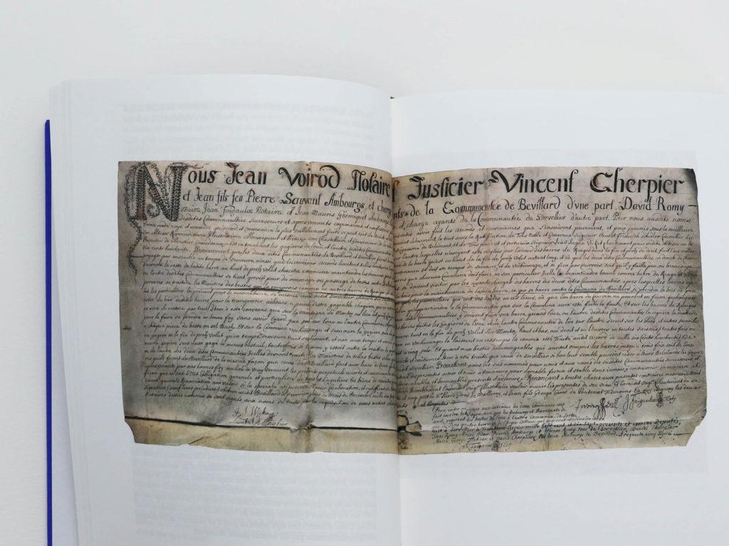Double page du livre Bévilard dans l'Histoire comportant une archive manuscrite de Jean Voirod. notaire, et Vincent Cherpier, justicier daté de 1717.