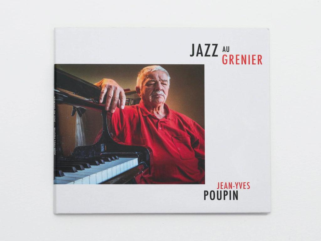 Recto de la couverture d'album Jazz au Grenier de Jean-Yves Poupin. Le portrait photographique de Poupin réalisé par Yves Meylan occupe le milieu de la couverture. Sur le dernier tiers, figure la composition typographique minimaliste du titre de l'album et du nom de l'artiste.