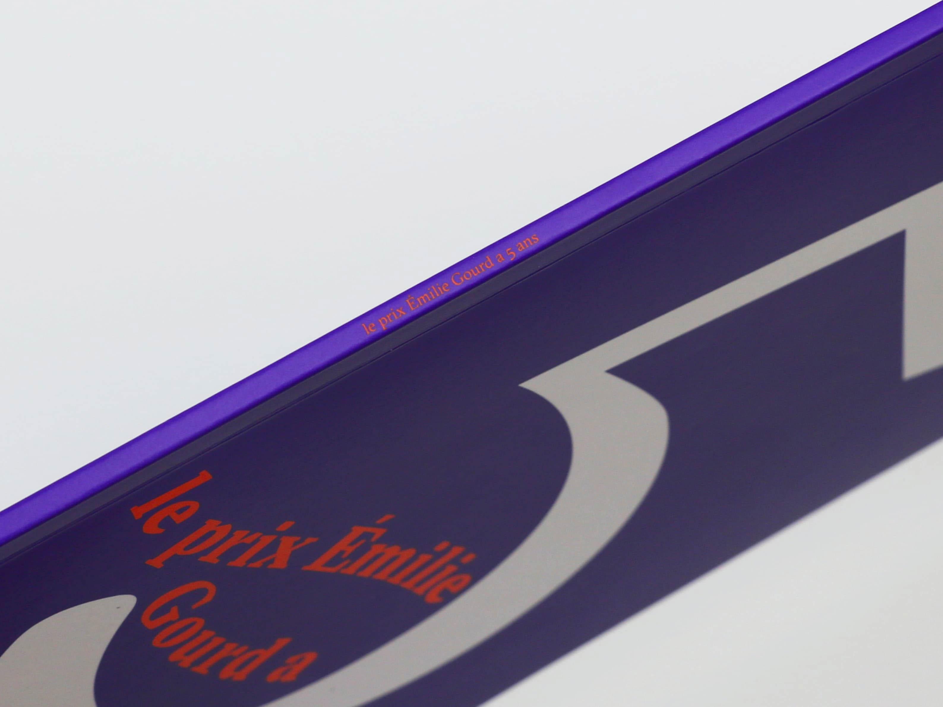 Tranche de la Brochure du Prix Emilie Gourd — sur la tranche violette est inscrit le prix Emilie Gourd a 5 ans  dans la police de caractère Sectra de Grilli Type et en couleur orange.